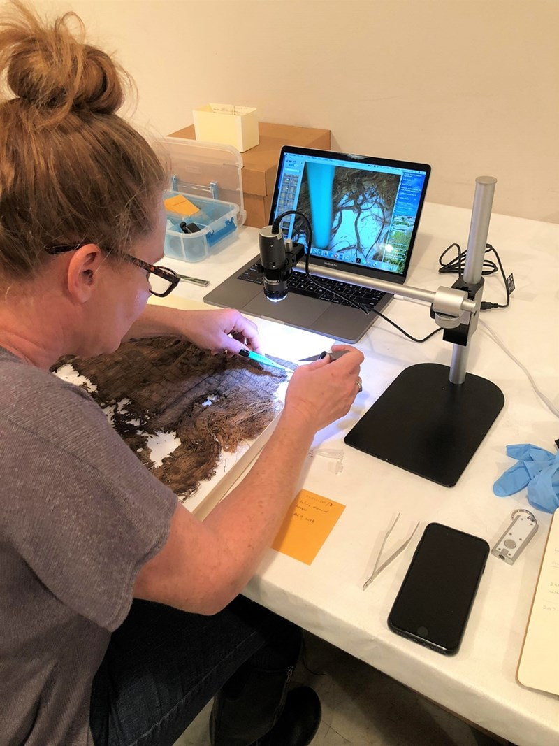 Elizabeth Horton takes a very small fiber sample from an Ozark bluff shelter textile for further analysis later.