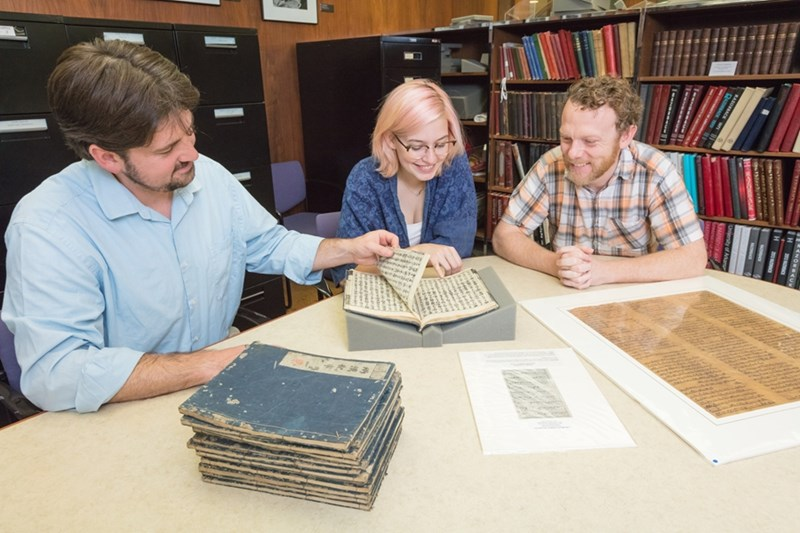Joshua Youngblood, Claire Hutchinson and Josh Smith examine 17th-century Japanese woodblock prints.