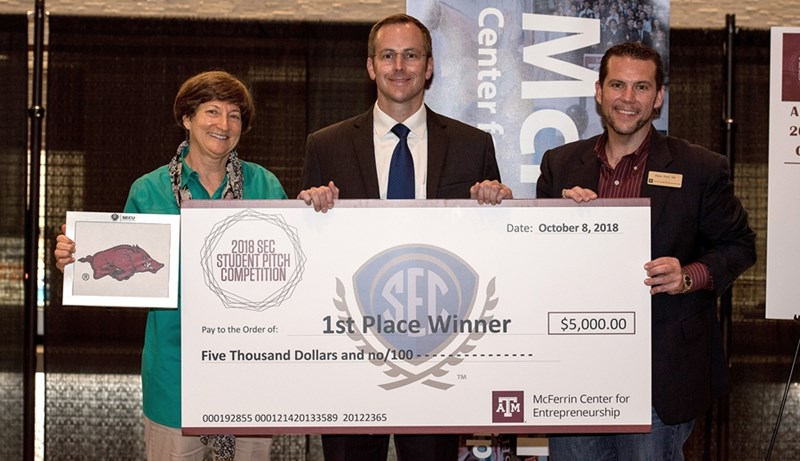 Jared Greer, center, receives the winner's check at the 2018 SEC Student Pitch Championship, with Carol Reeves, left, of the University of Arkansas and Blake Petty, right, of Texas A&M University.