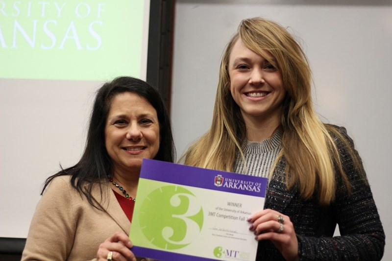 Aubree Hawley accepts the Three Minute Thesis winner award from Kim Needy, dean of the Graduate School and International Education.