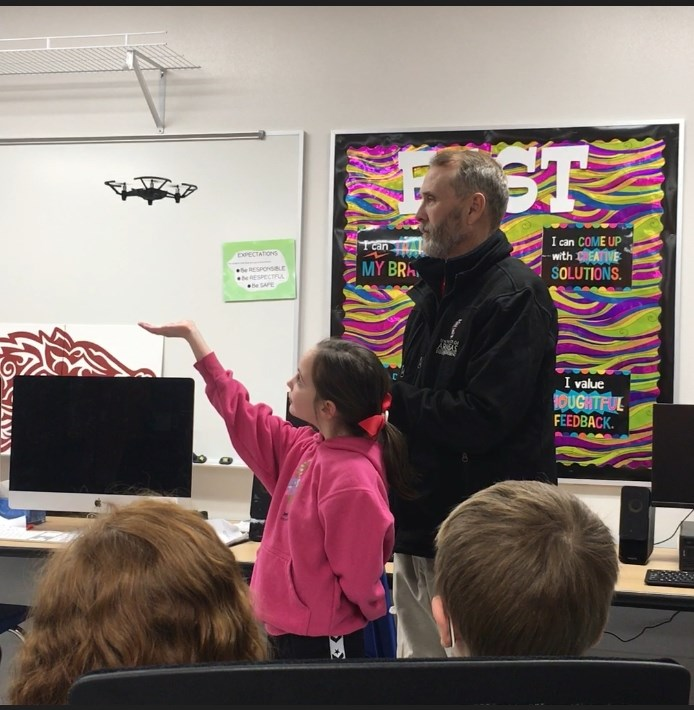 Isabella Earley, a student at Gentry Primary, watches a drone during a presentation from Rich Ham, associate director of the Operations Management graduate program. A partnership between the MSOM program and Gentry Public Schools is giving students a chance to learn about drones.