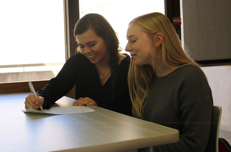A Career Development Center student worker assists a UA student with her resume.