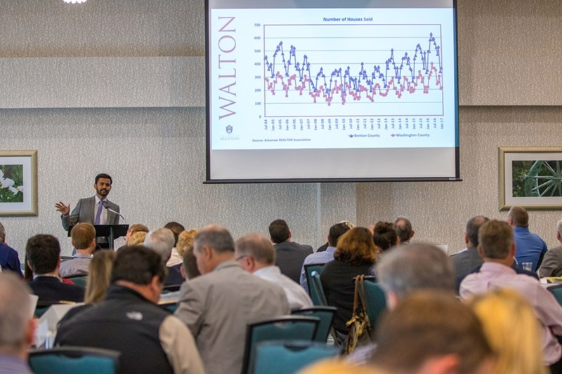 Mervin Jebaraj, director of the Center for Business and Economic Research , delivers his Quarterly Business Analysis report to a packed house in Fayetteville.