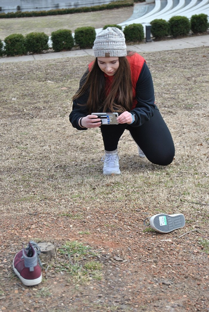 Kyra Vreeland, an architecture student, photographs a pair of shoes as part of the design thinking workshop for honors students, led by Beth Tauke and held in February on the U of A campus.