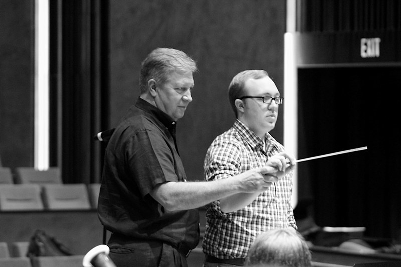 Christopher Knighten works with a University of Arkansas Conducting Symposium participant