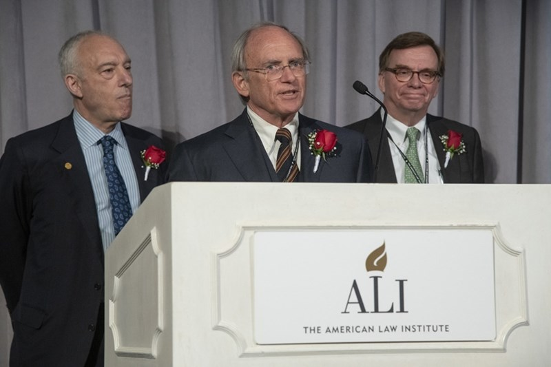 Professor Mark Killenbeck speaking at the American Law Institute Life Member Induction, along with William J. Perlstein, Life Class Committee member and senior deputy counsel at the Bank of New York Mellon Corporation (left) and John Beisner, Life Class Committee chair, ALI Council member and partner at Skadden, Arps, Slate, Meagher & Flom LLC in Washington, D.C.
