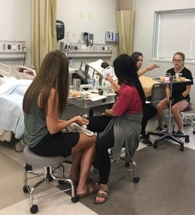 CDIS Students completing application-based assignment in nursing simulation lab
