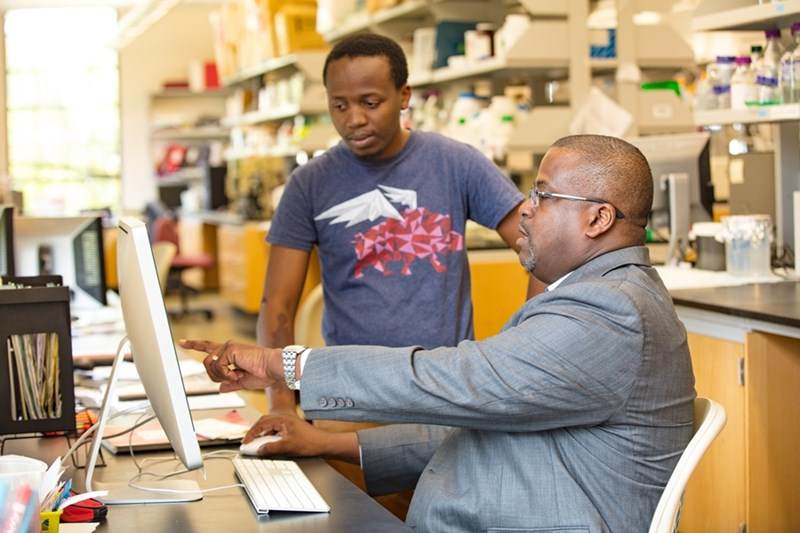 Paul Adams, associate professor of biochemistry, works with a student researcher.