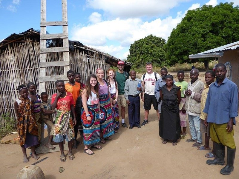 "Sarah Beth DeLay, near the center in a purple tank top, with colleagues in Mozambique. To respect cultural norms in their host country, the female students wear traditional ""capulanas."""