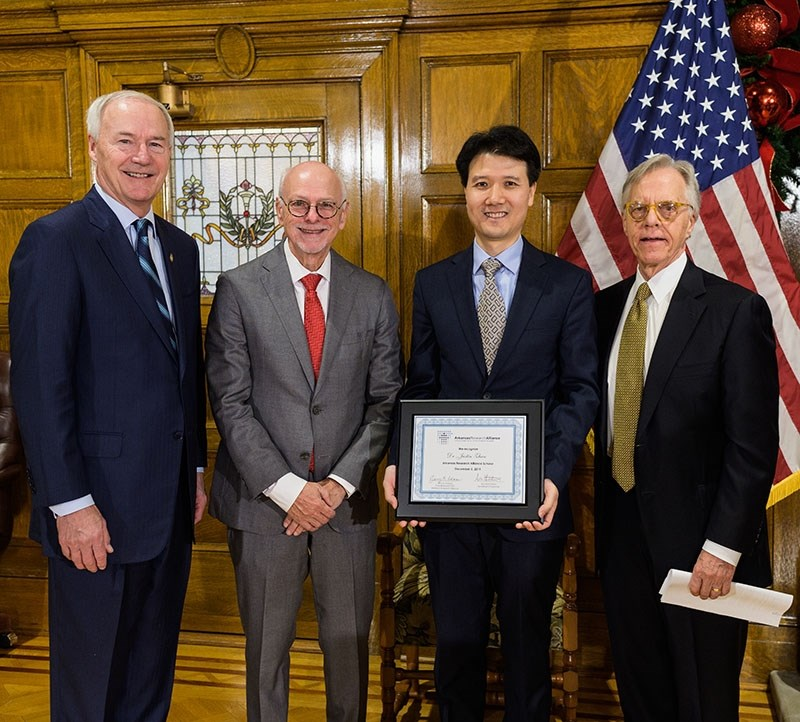 From left, Gov. Asa Hutchinson, Chancellor Joe Steinmetz, professor Justin Zhan and Jerry Adams, president and CEO of the Arkansas Research Alliance, at the Capitol Building in Little Rock.