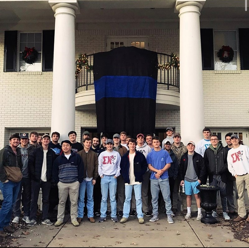 Members of the Sigma Chi fraternity stand under a black banner with a blue stripe, honoring Stephen Carr, a Fayetteville police officer who was killed Dec. 7.