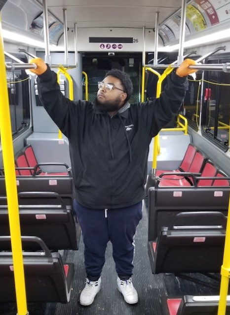 Dwayne Barber wipes the hand rails with sanitary wipes. He has been detailing buses for Razorback Transit for almost a year.