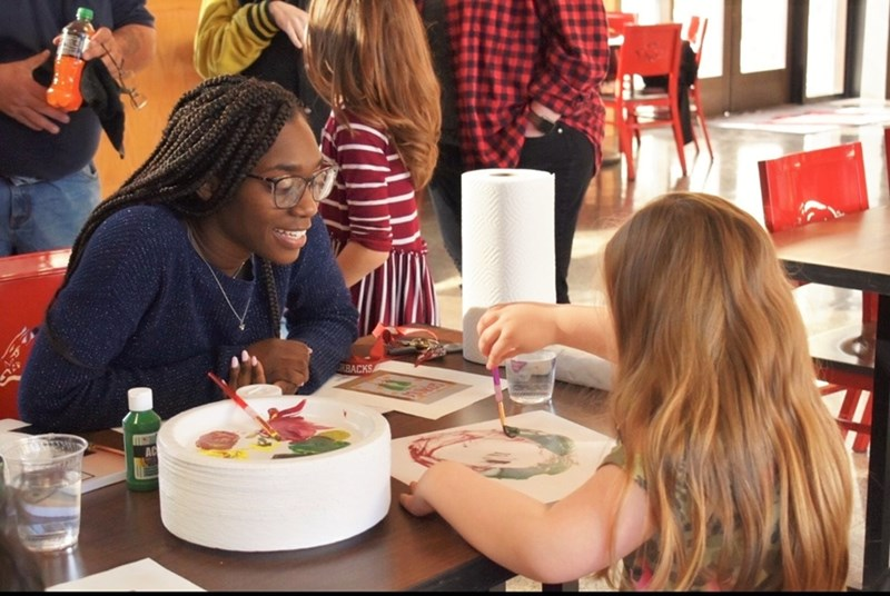 Student Jada Miller helps a child with crafts at an event to support Arkansas Hands and Voices.