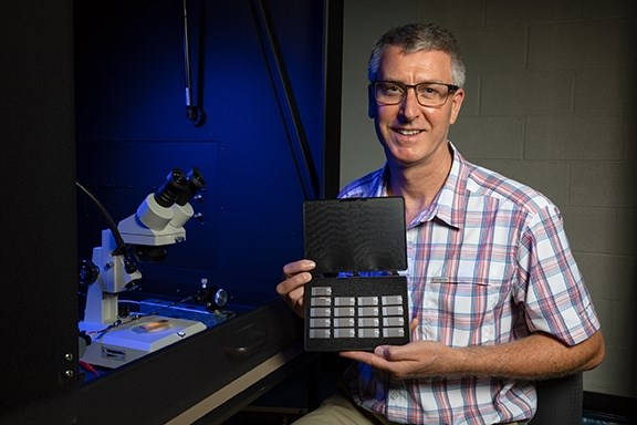 Paul Thibado, professor of physics, with sample energy-harvesting chips under development.
