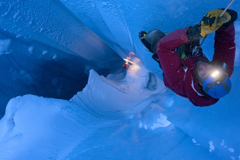 Matt Covington climbs into a moulin on the Greenland ice sheet.